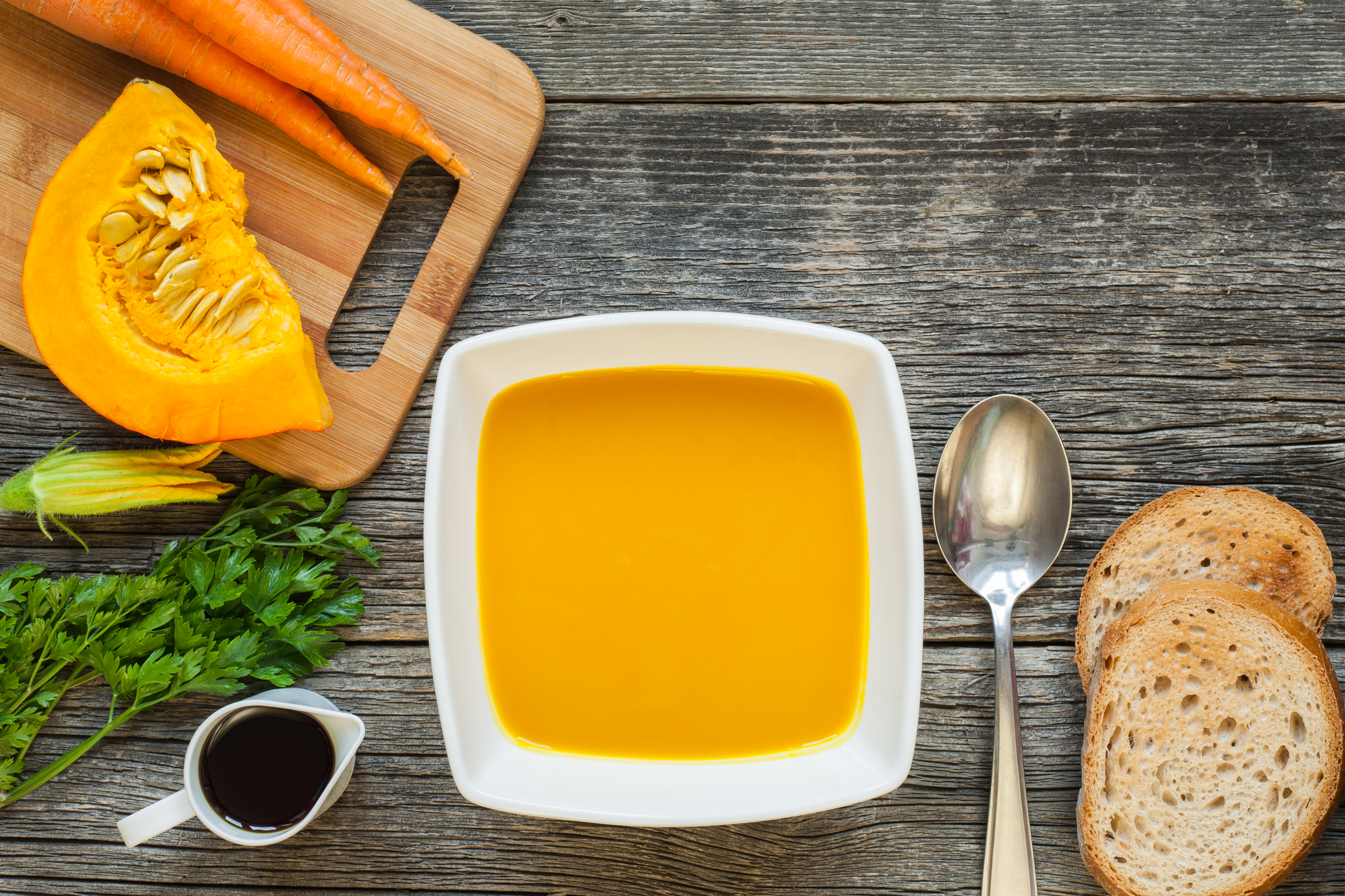 Hokkaido pumpkin soup in a white ceramic bowl with toasted bread